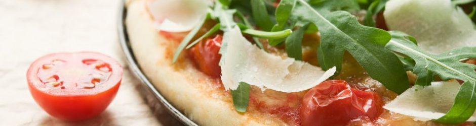 Pizza mit Ruccola und Tomaten