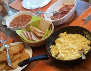 Englisches Frühstück mit Eiern, Bacon, Toast, Bohnen und Kartoffelecken